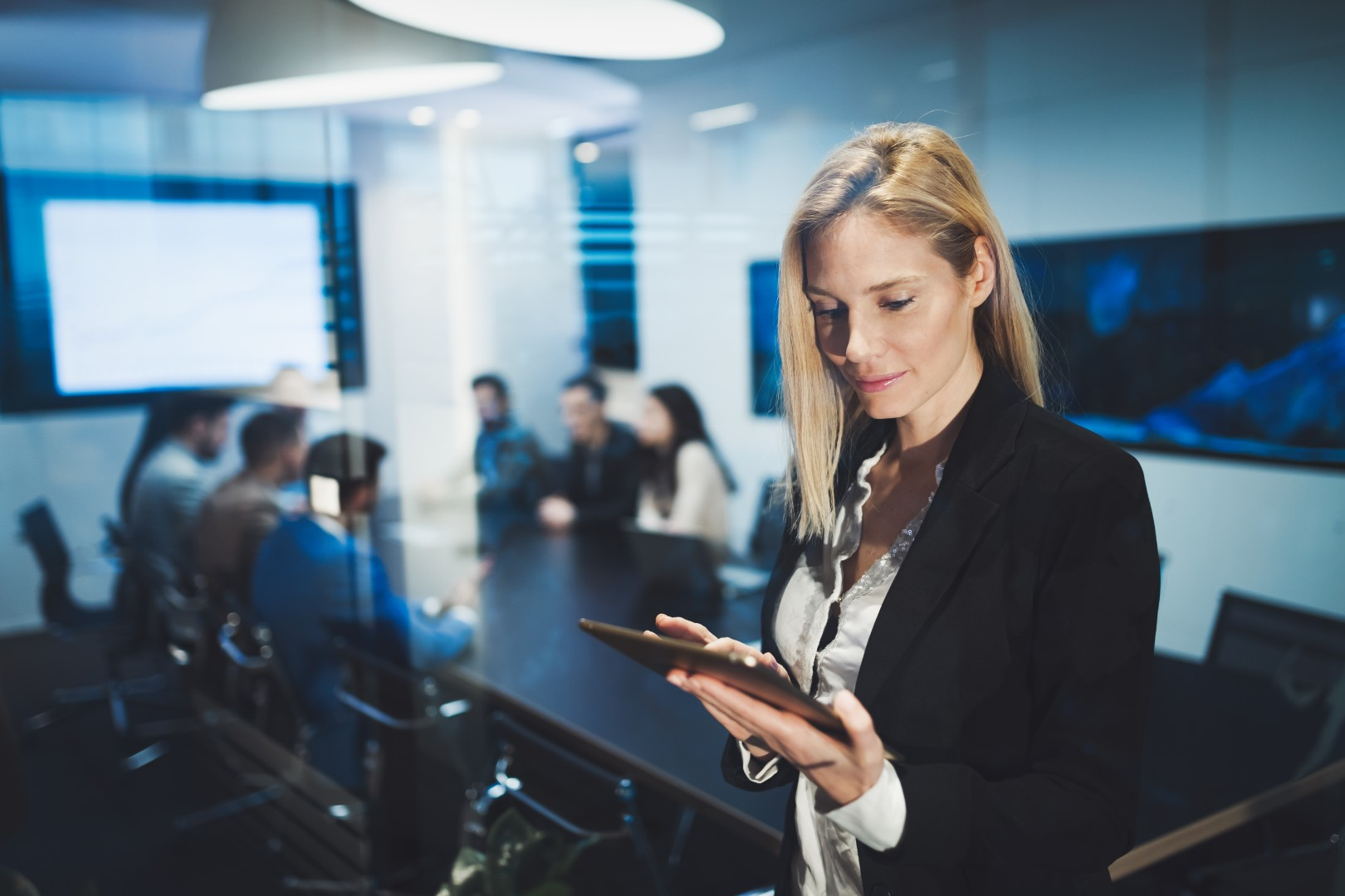 business-woman-holding-a-tablet-in-conference-4MXQG7Z